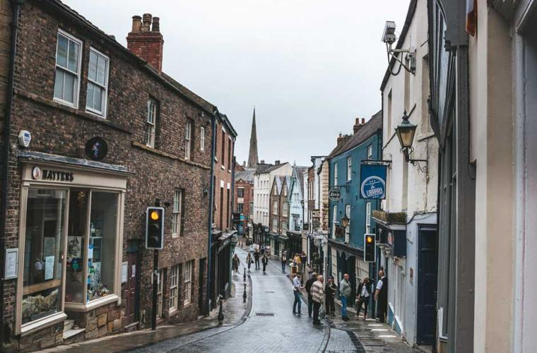 a high street with local shops in the rain