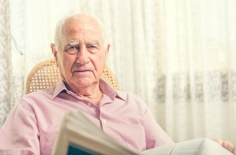 Older man, sat in a chair at home