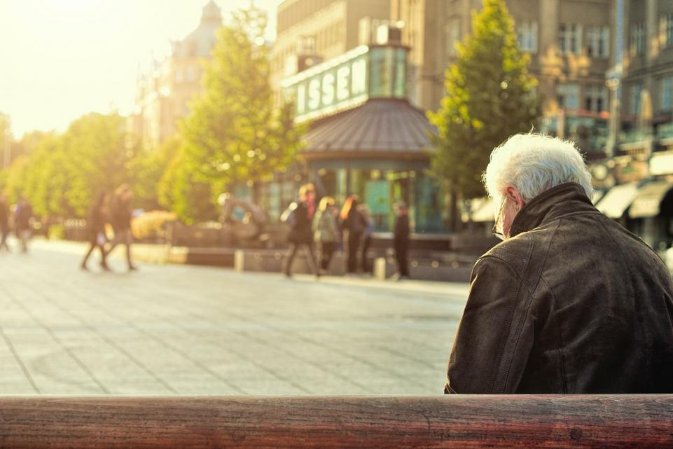 elderly man sitting alone on a bench in the town centre